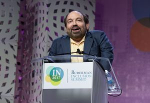 Danny Woodburn stands at a podium with a smile. The Ruderman Summit logo is on the podium.