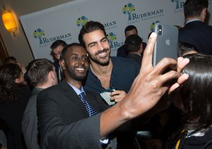 Nyle smiling at a phone next to a fan. A dozen people are milling about in the background.