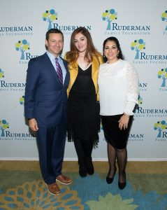 Jay and Shira Ruderman pose with Mandy Harvey in front of a wall of Ruderman logos.