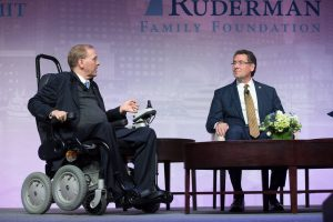 Congressman Jim Langevin sitting in his wheelchair, discussing Congressman Gregg Harper on the Summit stage.