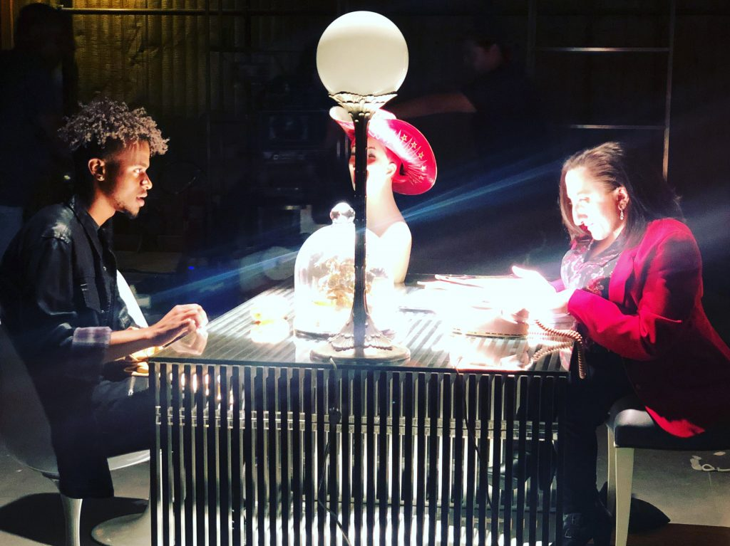 Nicole & a fellow intern at a table facing each other in a dimly lit room with a bright lamp in the center of the table. They are acting.