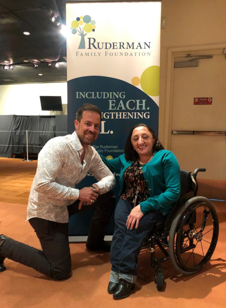 Kurt Yaeger kneeling on the ground to the left of Nicole Evans, smiling at the camera, in front of a Ruderman Family Foundation standing banner.
