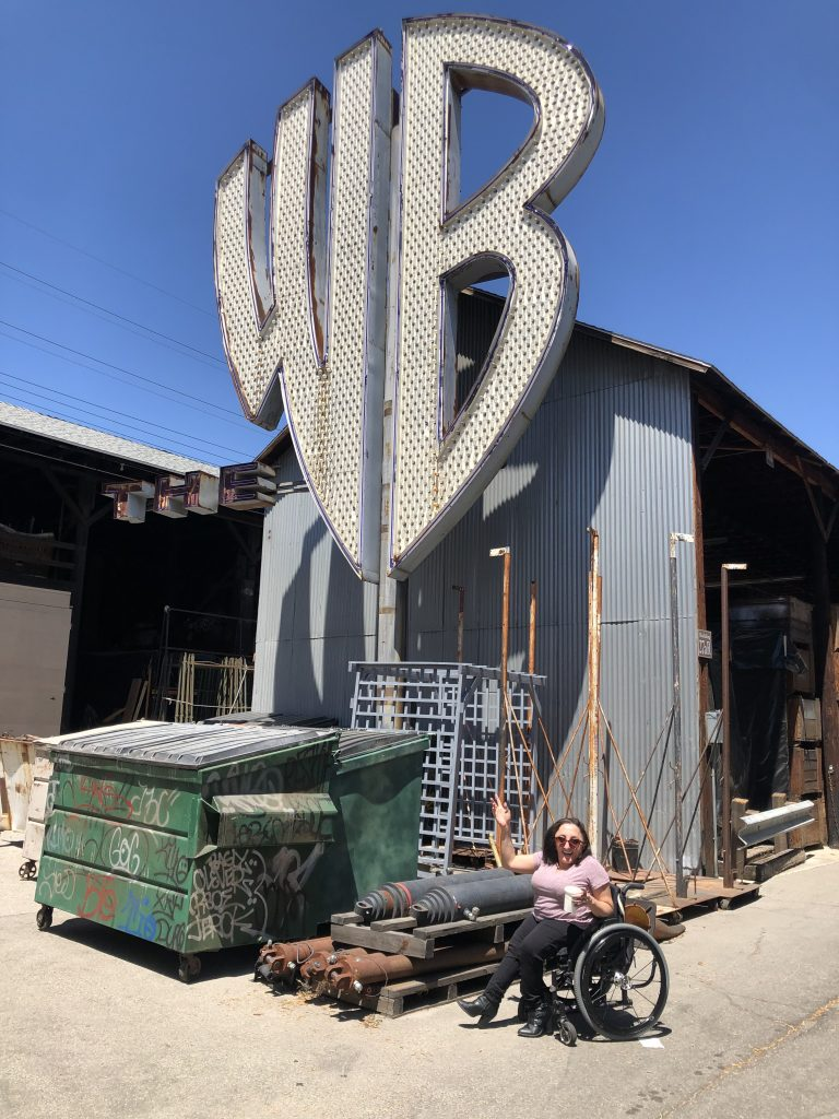 Nicole Evans below a big, white, Warner Brothers WB logo sign outside.